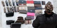 An unidentified vendor display fake designer bags and belts for sale near the Spanish steps in Rome on January 4, 2012. Handbags are displayed on a white sheet to make them easy to wrap up. The bags can be bought for 30 to 50 euros each. AFP PHOTO / GABRIEL BOUYS (Photo credit should read GABRIEL BOUYS/AFP/Getty Images)