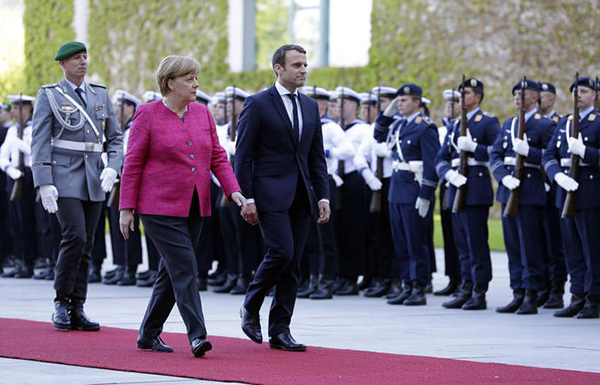New French President Emmanuel Macron is welcomed by German Chancellor Angela Merkel with a military ceremony in Berlin Monday, May 15, 2017, during his first foreign trip after his inauguration the day before. (ANSA/AP Photo/Michael Sohn) [CopyrightNotice: Copyright 2017 The Associated Press. All rights reserved.]