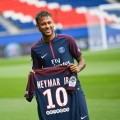 """TOPSHOT - Brazilian superstar Neymar poses with his new jersey during his official presentation at the Parc des Princes stadium on August 4, 2017 in Paris after agreeing a five-year contract following his world record 222 million euro ($260 million) transfer from Barcelona to Paris Saint Germain's (PSG). Paris Saint-Germain have signed Brazilian forward Neymar from Barcelona for a world-record transfer fee of 222 million euros (around $264 million), more than doubling the previous record. Neymar said he came to Paris Saint-Germain for a """"bigger challenge"""" in his first public comments since arriving in the French capital. / AFP PHOTO / Lionel BONAVENTURELIONEL BONAVENTURE/AFP/Getty Images"""