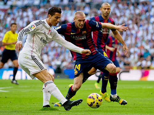 MADRID, SPAIN - OCTOBER 25:  Cristiano Ronaldo of Real Madrid CF looks to cross the ball under pressure from Jeremy Mathieu of Barcelona during the La Liga match between Real Madrid CF and FC Barcelona at Estadio Santiago Bernabeu on October 25, 2014 in Madrid, Spain.  (Photo by Gonzalo Arroyo Moreno/Getty Images)